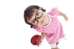 Pequeña pupila que come la manzana Imagen de archivo