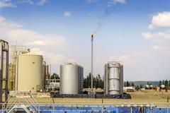 Pequeña refinería de petróleo al lado de la grande pradera, Alberta, Canadá foto de archivo
