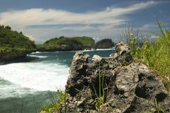 Pequeña roca con los acantilados enormes por la playa de Watu Karung Fotografía de archivo libre de regalías