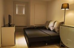 Pequeña sala de estar con el sofá cama abierto Foto de archivo libre de regalías