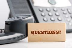 Pequeña señalización para las preguntas sobre el escritorio del teléfono Fotos de archivo