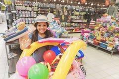Pequeña señora sonriente hilarante entre los juguetes en supermercado foto de archivo libre de regalías