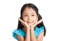 Pequeña sonrisa asiática muy feliz de la muchacha con la barbilla en las manos Fotos de archivo libres de regalías