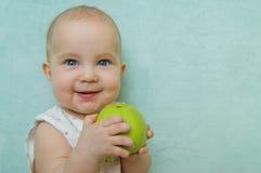 Pequeña sonrisa del bebé que come la manzana Fotografía de archivo libre de regalías