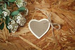 Pequeña tarjeta del corazón con las flores blancas y las hojas del verde en el fondo de madera de la textura Deseos de las celebr Imagenes de archivo