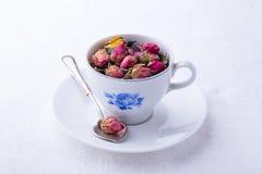 Pequeña taza con té seco de las rosas foto de archivo libre de regalías