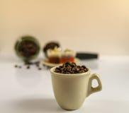 Pequeña taza cremosa de granos de café deliciosos Fotos de archivo libres de regalías