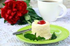 Pequeña torta en una placa con una taza de café Foto de archivo libre de regalías