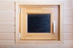 Pequeña ventana en una pared de madera ligera en una sauna Foto de archivo