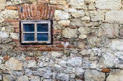 Pequeña ventana en una pared de piedra Imagen de archivo