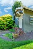 Pequeña vertiente al aire libre gris con paisaje del patio trasero. Fotografía de archivo