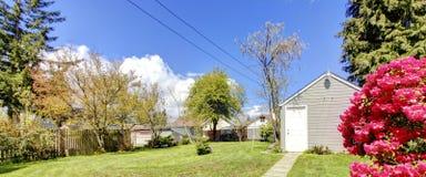 Pequeña vertiente azul con paisaje de la primavera del patio trasero. Imagenes de archivo