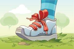 Pequeña zapatilla de deporte en la hierba Fotografía de archivo