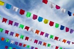Pequeñas banderas coloridas lindas en la ejecución de la cuerda afuera para los wi del día de fiesta Imagen de archivo