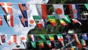 Pequeñas banderas de los países diferentes del alboroto del mundo en el viento contra los edificios del cielo y de la ciudad almacen de video