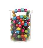 Pequeñas bolas de madera coloridas en un beneficiario de cristal Fotografía de archivo