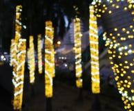 Pequeñas bombillas borrosas de la Navidad del oro amarillo que cuelgan y envolver alrededor de árboles de coco imagen de archivo libre de regalías