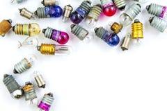 Pequeñas bombillas coloreadas viejas en un fondo blanco Imagen de archivo libre de regalías