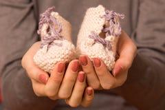 Pequeñas botas en las manos de la madre Imagen de archivo