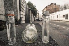 3 pequeñas botellas abandonadas vacías del alcohol en la calle vacía en W foto de archivo libre de regalías
