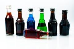 Pequeñas botellas del alcohol colorido Fotos de archivo libres de regalías