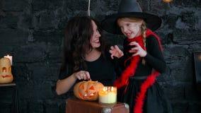 Pequeñas brujas de Childs en Halloween en un fondo negro, muchacha que sostiene la calabaza con una vela ardiente almacen de metraje de vídeo