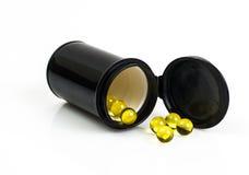 Pequeñas cápsulas de gelatina amarillas redondas en tarro negro Imagen de archivo