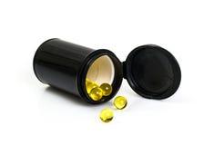 Pequeñas cápsulas de gelatina amarillas redondas en tarro negro Imágenes de archivo libres de regalías