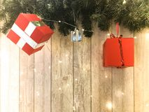 Pequeñas cajas de regalo festivas rojas lindas, la Navidad, la decoración del Año Nuevo en el fondo de las ramas de árbol de navi imagen de archivo