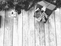 Pequeñas cajas de regalo de vacaciones blancos y negros lindas, la Navidad, la decoración del Año Nuevo en el fondo de las ramas  fotografía de archivo
