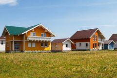 Pequeñas casas coloreadas modernas construidas en el campo contra un cielo azul con las nubes fotos de archivo
