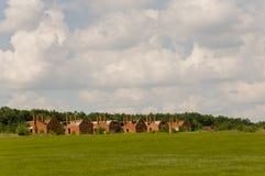 Pequeñas casas del ladrillo del color anaranjado en el suburbio Hierba verde y árboles alrededor Antes de lluvia Pueblo Foto de archivo