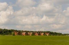 Pequeñas casas del ladrillo del color anaranjado en el suburbio Hierba verde y árboles alrededor Antes de lluvia Pueblo Fotos de archivo libres de regalías
