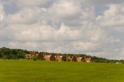 Pequeñas casas del ladrillo del color anaranjado en el suburbio Hierba verde y árboles alrededor Antes de lluvia Pueblo Fotografía de archivo
