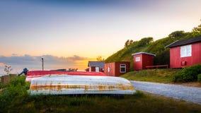 Pequeñas casas del ` s de los pescadores con la colocación de los botes al revés en la hierba en la puesta del sol Imagenes de archivo