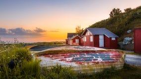Pequeñas casas del ` s de los pescadores con la colocación de los botes al revés en la hierba en la puesta del sol Fotos de archivo libres de regalías