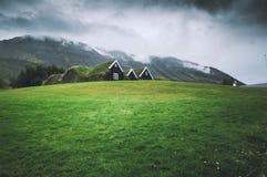 Pequeñas casas en un campo verde con el cielo oscuro imagenes de archivo