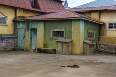 Pequeñas casas viejas en el pueblo Una pila de abono del caballo en el camino fotografía de archivo