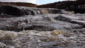 Pequeñas cascadas y flujo a lo largo de un alto río escocés de las montañas en sutherland durante noviembre metrajes