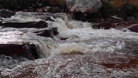 Pequeñas cascadas y flujo a lo largo de un alto río escocés de las montañas en sutherland durante noviembre almacen de video