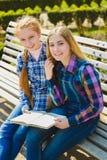 Pequeñas colegialas bonitas que leen un libro y que se sientan en el banco al aire libre Fotografía de archivo libre de regalías