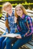Pequeñas colegialas bonitas que leen un libro y que se sientan en el banco al aire libre Fotos de archivo libres de regalías
