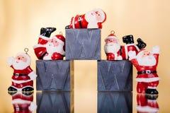 Pequeñas decoraciones del ` s de Papá Noel en fondo brillante de oro con W, w, w Imagen de archivo