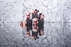 Pequeñas decoraciones del ` s de Papá Noel en fondo brillante de plata chispeante con W, w, w Imagenes de archivo
