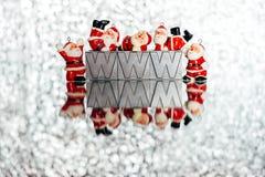 Pequeñas decoraciones del ` s de Papá Noel en fondo brillante de plata chispeante con W, w, w Imagen de archivo