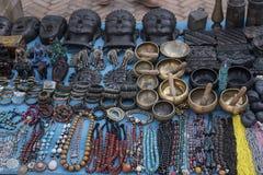 Pequeñas estatuas, collares y otros artículos del recuerdo en venta en el mercado de la calle Fotografía de archivo libre de regalías