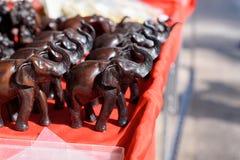 Pequeñas estatuas de elefantes en la tabla roja Fotos de archivo