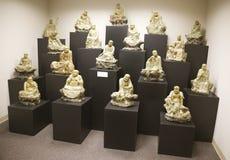 Pequeñas estatuas de mármol japonesas de Buddah en la exhibición en un museo Imagen de archivo