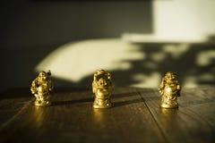 Pequeñas estatuas de oro hermosas de Buda que se colocan en la tabla de madera oscura en luz del sol Imagen de archivo
