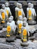 Pequeñas estatuas múltiples de Buda con las guirnaldas amarillas Imagen de archivo libre de regalías